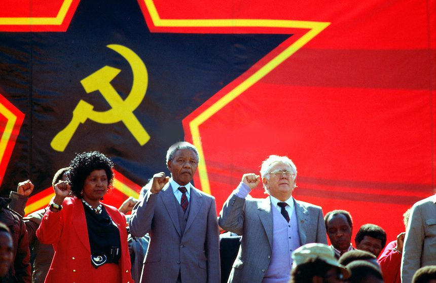 Nelson Mandela saluting at a South African Communist Party rally in 1990